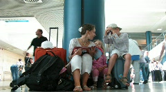 Mother with children sit about luggage in a hall of of the airport. Stock Footage