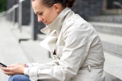 Young woman sitting on the stairs and using mobile phone, dolly shot Stock Footage