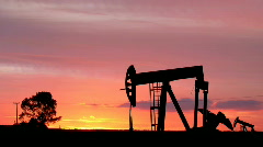Oil Pumping Silhouettes in the Sunset Across the Plains Stock Footage