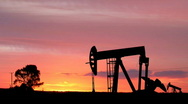 Stock Video Footage of Oil Pumping Silhouettes in the Sunset Across the Plains