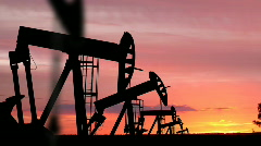 Stock Video Footage of Oil Pumping Rigs Silhouetted in the Sunset