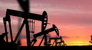 Oil Pumping Rigs Silhouetted in the Sunset Stock Footage