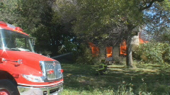 House fire +  firetruck, and firemen on scene Stock Footage