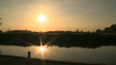 Sun over water and reflected in the water on the Norfolk Broads Stock Footage