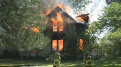 Huge fire, 2 story house falls over, fireman on the scene Stock Footage