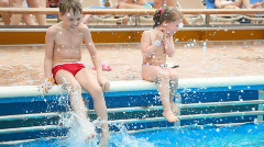 Boy and girl sits near outdoor swimming pool Stock Footage