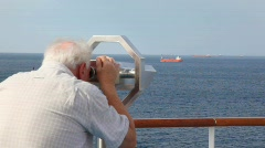 Aged man looks through stationary binocular on deck of cruise ship Stock Footage