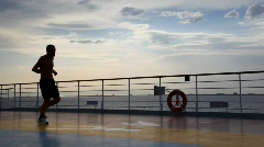 silhouette of man running on deck of cruise ship - stock footage