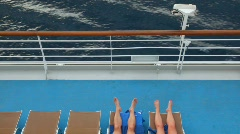 Legs of man and woman lying on deck chairs Stock Footage