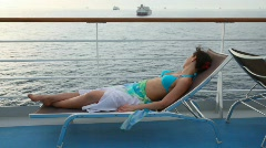 Woman lying on deckchair on deck Stock Footage