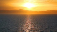 Sunset in sea, mountains in background Stock Footage