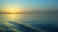Stock Video Footage of sunset above water cleaves by ship