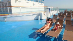 Mother and daughter in bikini lying on deckchairs Stock Footage
