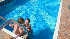 woman and girl having fun in swimming pool - stock footage