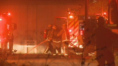 Firemen first on scene at a shed fire Stock Footage