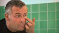 Man applying eye cream Stock Footage