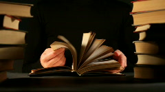 Hands and book over dark background Stock Footage