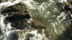 Rapid river water flows past glistening wet boulder rocks in sunshine Stock Footage