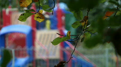 Children's playground with autumn leaves in foreground  - stock footage