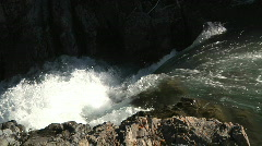 Stock Video Footage of rushing river water tumbles down rocky falls into black chasm audio