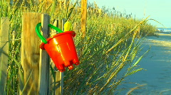 Child's pail and shovel on fence Stock Footage