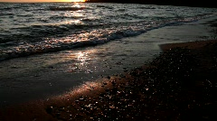 Stock Video Footage Sunlight in the surf of the sea at sunset. Stock Footage