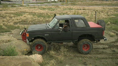 Ford bronco 4x4 spins out in mud rock boulder Stock Footage