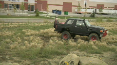 ford bronco 4x4 drives on grass and mud to boulders audio - stock footage