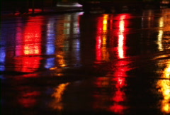 City lights reflected in wet street at night Stock Footage