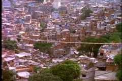 Slums of Rio de Janeiro, favallas, on hillside, tilt up to high rise luxury Stock Footage