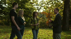 Teacher talking to students in park Stock Footage