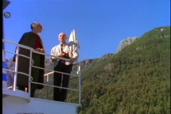 Crossing Andes mountain lake, POV from boat, two men watch from upper deck Stock Footage