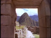 Stock Video Footage of Machu Picchu, Peru, The Andes, medium shot through gate, no people, tilt down