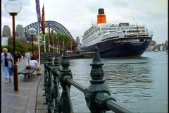 The Queen Elizabeth 2, QE2 stern with Sydney Harbor Bridge, gray sky Stock Footage