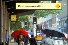 Sydney, crowds of people in rain with umbrellas, Commonwealth Bank sign Stock Footage