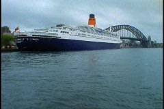 The Queen Elizabeth 2, QE2 from stern, wide shot with Sydney Harbor Bridge, tilt Stock Footage