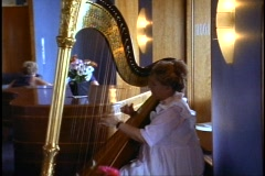 The Queen Elizabeth 2, QE2, harpist playing in Chart Room, medium close up Stock Footage