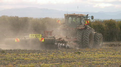 Tractor cultivating a bare field Stock Footage