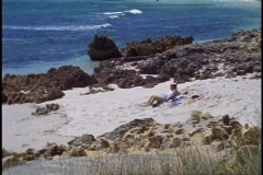 Australian coast, sea, green, sand, woman lying on beach, medium shot Stock Footage