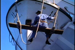 Workman painting one of the lifeboats of the Queen Elizabeth 2, medium shot Stock Footage