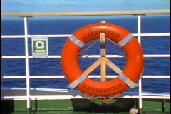 Queen Elizabeth 2, QE2 life ring buoy on rail, sea passing in background - stock footage