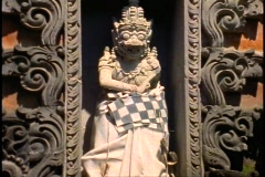 Bali, Temple, Balinese, medium close-up statue with drape tilt up Stock Footage