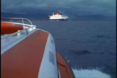 Queen Elizabeth 2, QE2 at anchor, approaching from tender, POV wide shot Stock Footage