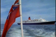 Queen Elizabeth 2, QE2 at anchor, on tender moving away, ensign waving Stock Footage