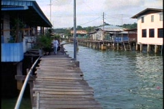 Brunei, water village houses and rickety walkway, medium shot, young people pass Stock Footage
