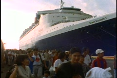 The Queen Elizabeth 2, QE2, ships bow, crowd of Filipinos crew passing Stock Footage