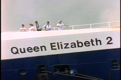 """The Queen Elizabeth 2, QE2, close up of """"Queen Elizabeth 2"""" on bow with people - stock footage"""