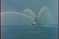 Fireboat spraying water, Queen Elizabeth 2, QE2, in Hong Kong Harbor, bow of Stock Footage
