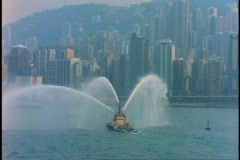 Fireboat spraying water, QE2, in Hong Kong Harbor, medium wide Stock Footage