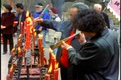 China, Xian, people lighting joss sticks at temple and praying medium shot Stock Footage